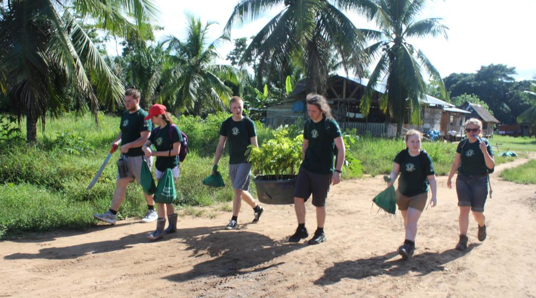 Projects Abroad volunteers take materials to the farm as part of the conservation work in the Amazon Rainforest in Peru.